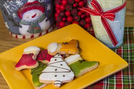 Christmas table with yellow plate of decorated Christmas cookies and a glass of milk photo