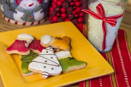 Holiday table with yellow plate of frosted Christmas cookies and millk for Santa photo