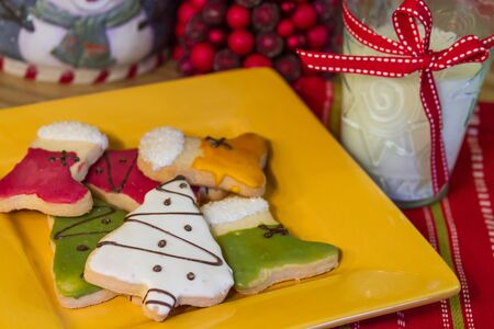 Decorated Christmas cookies on yellow plate, with a glass of milk on holiday table photo