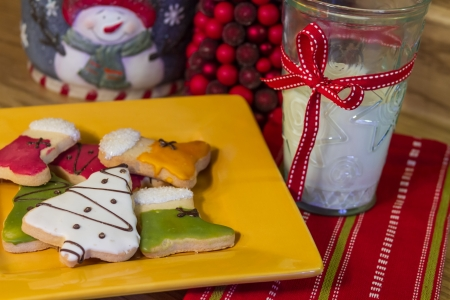 Holiday table with frosted Christmas cookies on yellow plate and glass of milk photo