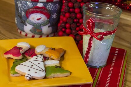 Cookies and milk for Santa on a yellow plate, with holiday cookie jar photo