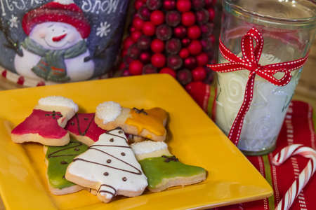 Frosted Christmas cookies on yellow plate with a glass of milk photo