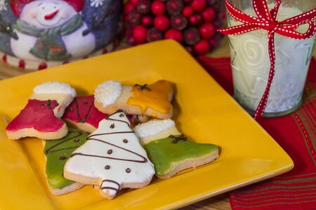 Yellow plate of frosted Christmas cookies and a glass of milk on a holiday decorated table photo