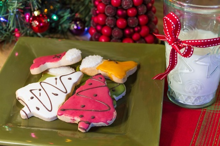 Holiday decorated cookies on green plate, on Christmas table with glass of milk photo