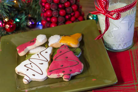 Frosted holiday cookies on green plate with glass of milk on a holiday table photo