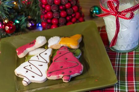 Holiday table with frosted Christmas cookies on green plate and glass of milk
