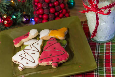 Christmas cookies on a green plate with a glass of milk, and Christmas tree photo