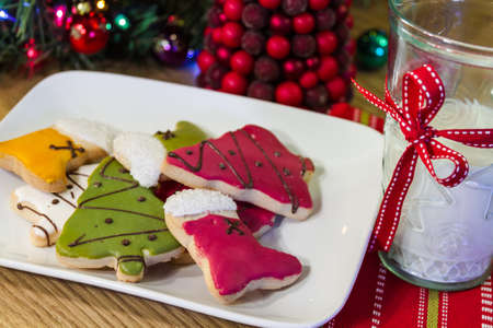 Christmas cookies on a white plate with a glass of milk photo