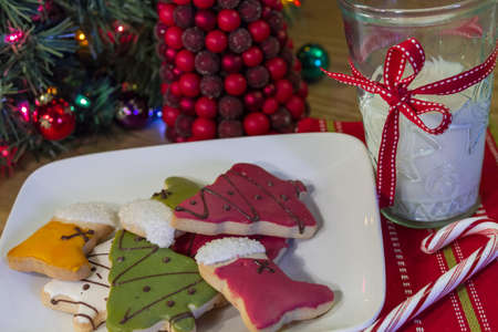 Frosted Christmas cookies on a white plate with a glass of milk, on a holiday table photo