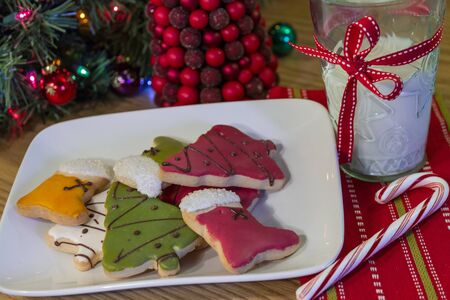 Decorated Christmas cookies on a white plate, with a glass of milk and a candy cane photo
