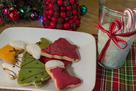 Colorful frosted Christmas cookies on a white plate and a glass of milk, on a holiday decorated table photo