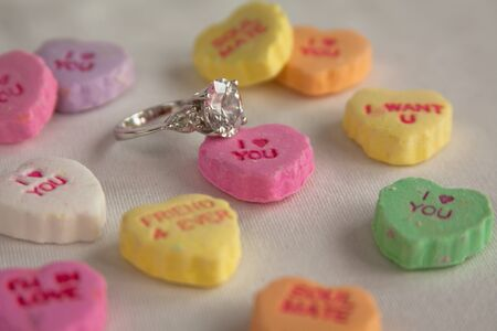 Colorful candy hearts with diamond ring for Valentine proposal Imagens