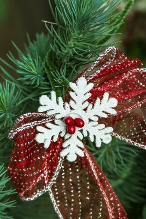 White snowflake with red bow in evergreen Christmas tree photo