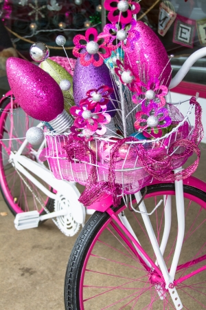 Hot pink cruiser bike filled with Christmas decorations photo