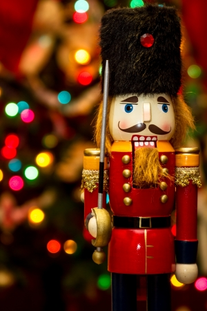 nutcracker: Soldier nutcracker statue standing in front of decorated Christmas tree