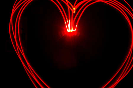 Multiple red heart light streaks made by light painting Stock Photo