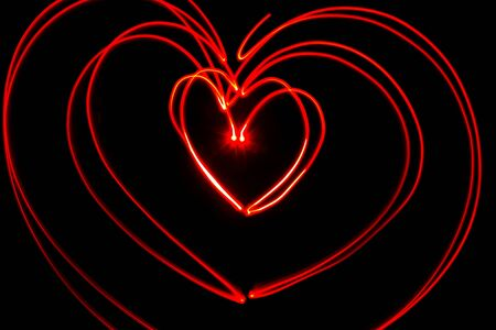 Red heart shaped light streaks made by light painting