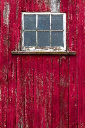 Old window on abandoned red barn with textured old split wood photo