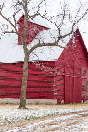 Abandoned red barn on cold winter day with gray skies and snowy ground photo