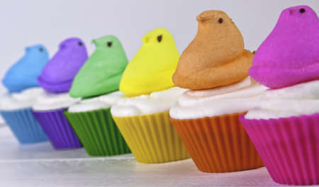 Colorful Easter cupcakes with Easter marshmallow chicks arranged in a rainbow Stock Photo