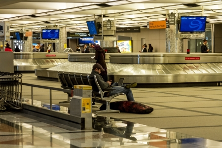 denver co: Man on computer and phone waiting at baggage claim in airport