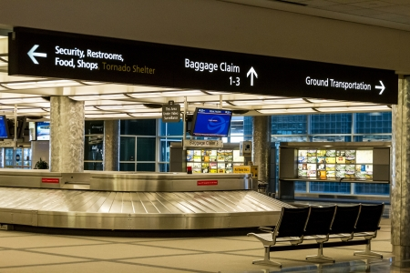 Baggage claim with airport directional signs above Editöryel
