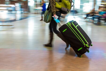 denver co: Woman walking quickly pulling green and black luggage in busy airport