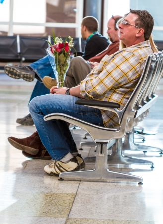 Man waiting in airport with bouquet of flowers Stock Photo - 17403465