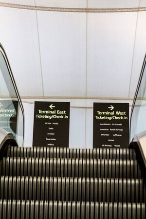 informational: Airport informational signs at the top of escalator