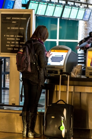 Woman in airport using electronic ticketing machine to check in for flight