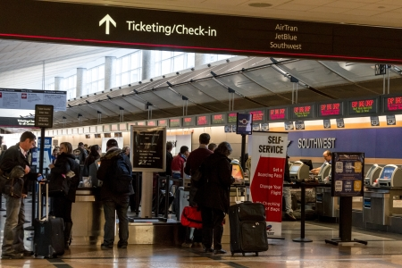 People waiting in ticketing check in lines at busy airport
