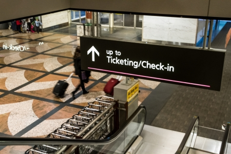 denver co: Escalator going down with Ticketing Check In sign in airport Editorial