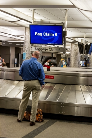 Man standing by baggage claim waiting for luggage Publikacyjne