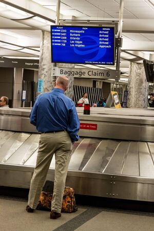 Man standing by baggage carousel waiting for luggage in airport