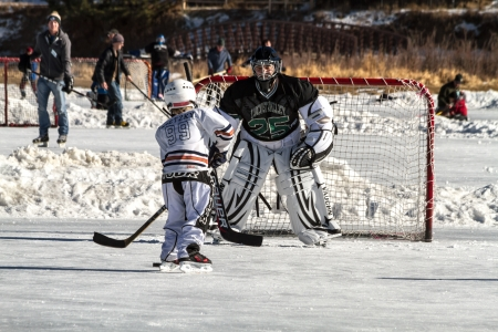 2 boys dressed in ice hockey gear playing on outdoor skating rink