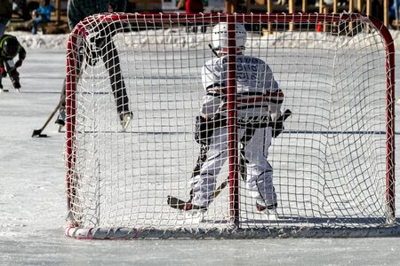 Young boy defending hockey goal, playing hockey on outdoor skating rink