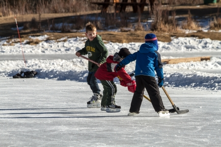 Little boys learning to play hockey on outdoor skating rink