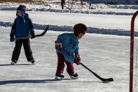 Little boy learning to play hockey on outdoor skating rink