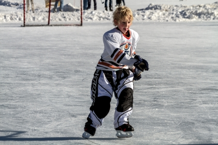 Young boy skating in hockey uniform with stick on outdoor hockey rink