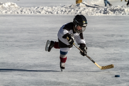 Little boy dressed in hockey gear skating after hockey puck, on outdoor skating rink