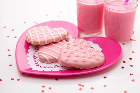3 decorated pink Valentine cookies on pink plate with strawberry milk photo