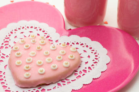 Pale pink heart cookie with white pearls on pink plate for Valentines Day photo