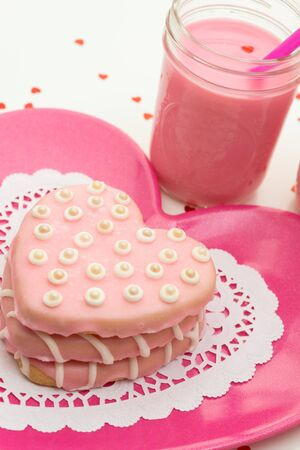 Stack of pink heart shaped cookies on pink plate with glass of strawberry milk photo