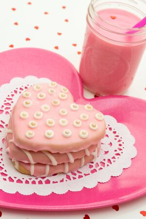 Stacked hand decorated pink heart cookies on a pink plate with glas of milk Stock Photo - 17592519