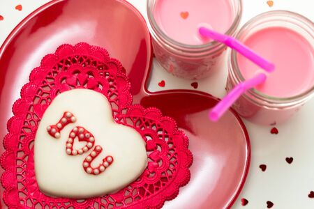 Valentines Day I love you decorated cookie on red heart shaped plate with 2 glasses of strawberry milk photo
