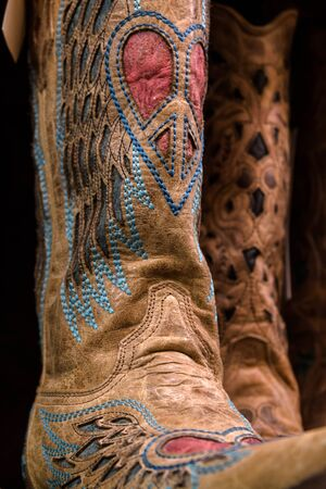 Womens cowgirl boots decorated with a peace sign in the shape of a heart