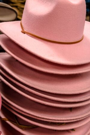 Stack of light pink womens cowboy hats with a brown band