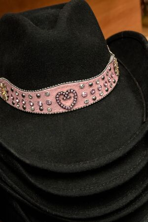 jeweled: Stack of black cowgirl hats with jeweled heart with pink gems on a pink band Stock Photo