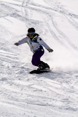 Female snowboarder swishing down hill at Ski Days during 50 Year Steamboat Springs winter celebration Editorial