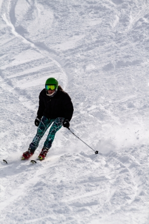 Female skier skiing down hill in fresh snow at Ski Days during 50 Year Steamboat Springs winter celebration